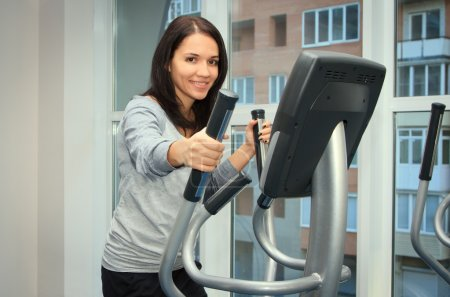 Young woman doing exercise on a elliptical trainer...