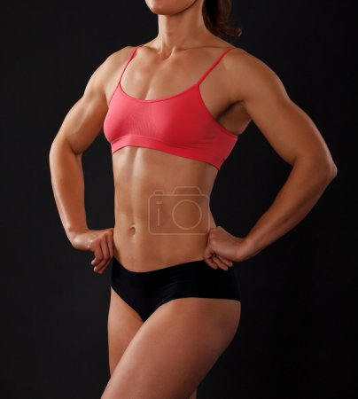 Photo for Muscular female body against black background. - Royalty Free Image