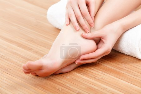Photo for Female feet and hands with a white rolled towe - Royalty Free Image