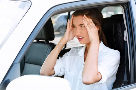 Troubles on the road, girl touches her forehead by hands