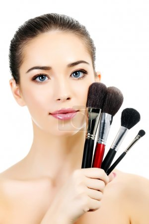 Pretty woman with cosmetic brushes, white background