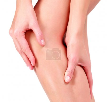 Woman holding sore knee, on white background