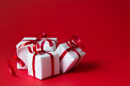 Photo for White gift box with red ribbon isolated on red color background - Royalty Free Image