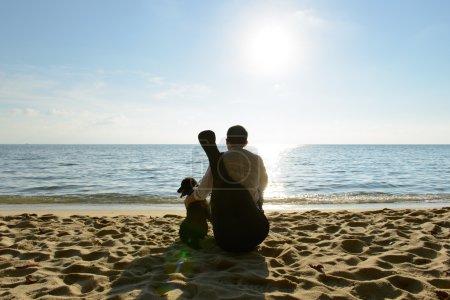 Photo pour Homme seul avec son chien et sa guitare à la plage - image libre de droit
