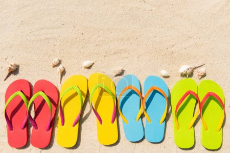 Photo for Four pairs of flip flops in a row on beach - Royalty Free Image