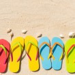 Four pairs of flip flops in a row on beach...