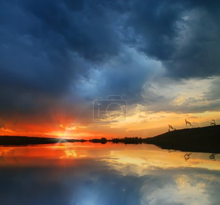 Photo for Spectacular sunrise or sunset with blue and orange reflected in water. - Royalty Free Image