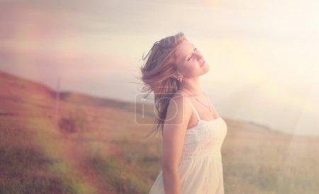 Photo pour Tranquillité d'une jeune fille les yeux fermés dans un champ sur la nature - image libre de droit