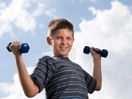 Boy lifting dumbbells outdoors