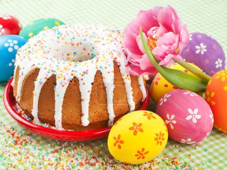 easter cake, tulip and colorful eggs on kitchen table