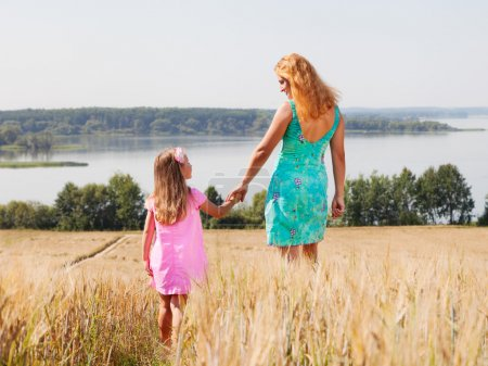 Mother and daughter walking in summer field