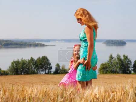 Little girl hugging her mother in a wheat field near lake on a s