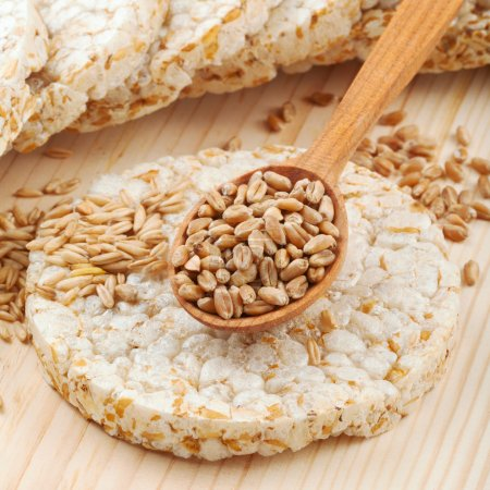 Photo for Crispbread, cereal crackers and wooden spoon with grain - Royalty Free Image