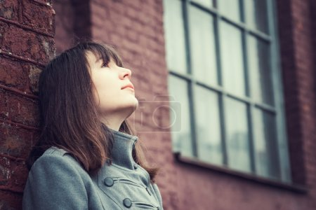 Photo for Pensive beautiful young girl standing near a brick wall and looking up - Royalty Free Image
