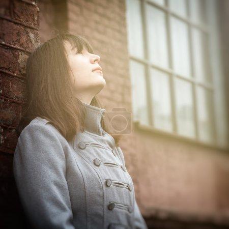 jeune fille debout près d'un mur de briques et levant les yeux