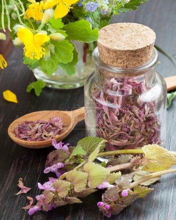glass bottle with healing herbs, healthy flowers and wooden spo