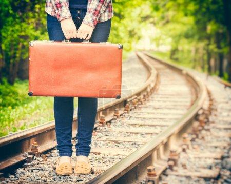 Photo for Girl with retro vintage suitcase on railway, retro stylized - Royalty Free Image