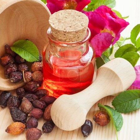 essential oil in glass bottle, dried rose-hip berries in wooden