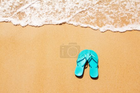 Photo for Flip flops on a sandy ocean beach - Royalty Free Image