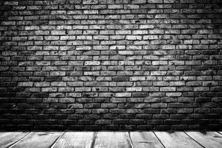 Dark room with wooden floor and brick wall backgro...
