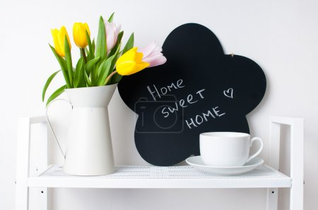 Photo for Home interior decoration: a bouquet of tulips in a jug, cup and saucer, and chalk board on the white shelves - Royalty Free Image