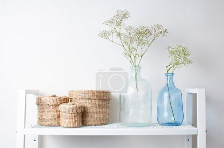 Photo for Home interior decoration: the branches in vintage bottles and baskets on white shelves - Royalty Free Image