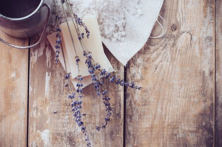 Photo pour Rustic country background, natural soap, lavender, salt and old cans on a wooden board, hygiene items for the bath and spa. - image libre de droit