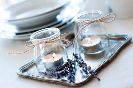 Photo pour Table à manger définissant au style provençal, avec des bougies, lavande, vintage vaisselle et coutellerie, gros plan. - image libre de droit