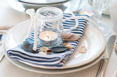 Photo pour Tableau définissant dans un style marin, avec des bougies, des coquillages et des serviettes de table rayés, gros plan - image libre de droit