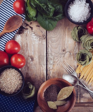 Photo for Food background, fresh vegetables, tomatoes, peppers, green spinach, salt, rice, pasta, spices and kitchen utensils on a wooden board, close-up, vintage style - Royalty Free Image