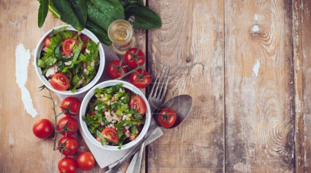 Photo for Dietary food background: vegetable salad with spinach, cherry tomatoes, barley porridge and olive oil on an old wooden board, vegan cuisine - Royalty Free Image
