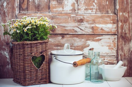 Photo for Flowers in a wicker basket, glass bottles and vintage milk can on wooden background, cozy home rustic decor, cottage living - Royalty Free Image