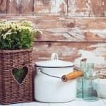 Flowers in a wicker basket, glass bottles and vint...