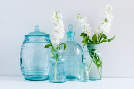 Photo for Vintage home decor, white matthiola flowers in different blue glass bottles vases and antique jars on a shelf by the wall - Royalty Free Image