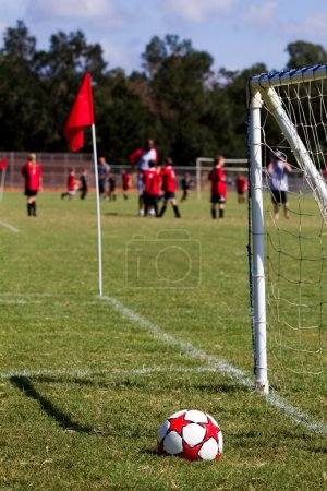 Photo for Soccer ball sits in the grass by the goal with a red flag marking the boundary lines of a practice field while a team plays in the background. - Royalty Free Image