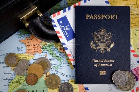 Photo pour Passeport USA, pièces étrangères et porte-documents s'asseoir sur une carte du monde pour un concept de voyage d'affaires internationales. - image libre de droit