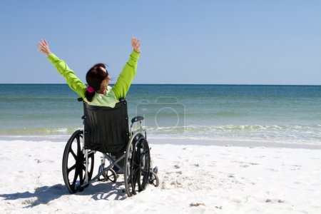 Photo for Woman with arms raised celebrates her achievement and success in the sunshine even with her disabilities in a wheelchair. - Royalty Free Image