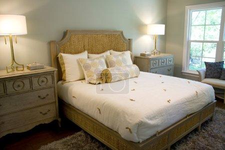 Photo pour Élégante chambre bien éclairée avec commode, lampes et tête de lit . - image libre de droit