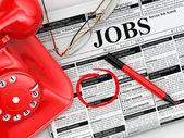 Hledání zaměstnání. noviny s reklamy, brýle a telefon