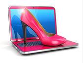Women's laptop. High heel shoes on keyboard.