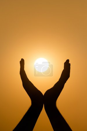 Photo for Hands holding the sun at yellow sunset background - Royalty Free Image