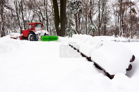 Red tractor cleaning park after snowfall