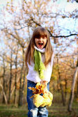 Shouting girl in the autumn forest with leaves and teddy bear