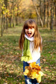Little girl shouting in the autumn forest and holding leaves
