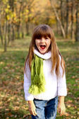 Shouting little girl in the autumn forest