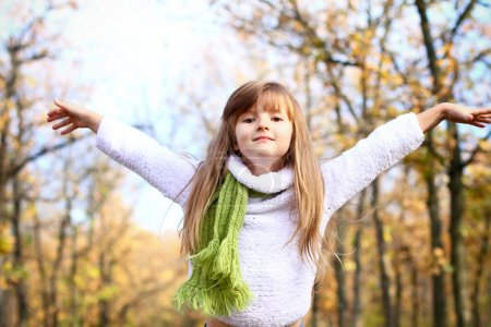 Little girl with hands up in the autumn forest