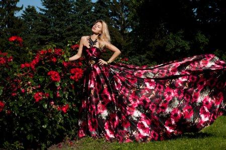 Photo pour Belle femme à la mode dans un jardin de roses - image libre de droit