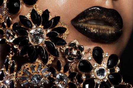 Photo pour Lèvres féminines avec bijoux dorés - image libre de droit