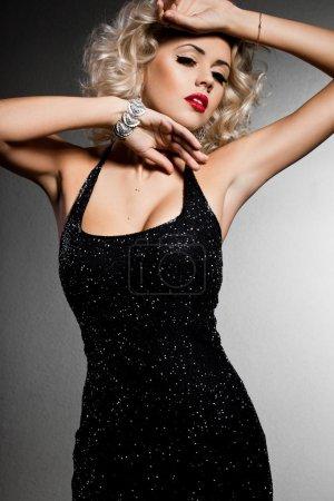 Photo pour Femme blonde souriante en robe noire - image libre de droit