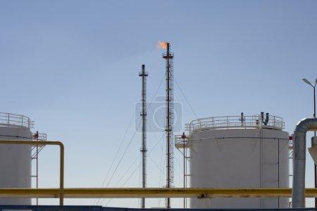 Photo pour Réservoirs de stockage et tours à gaz à flammes brûlantes dans une usine pétrochimique industrielle extrayant des combustibles fossiles de la terre - image libre de droit